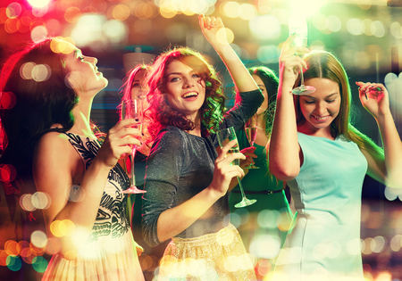 party, holidays, celebration, nightlife and people concept - smiling friends with glasses of champagne dancing in club