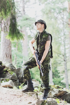 infantryman: hunting, war, army and people concept - young soldier, ranger or hunter with gun in forest Stock Photo