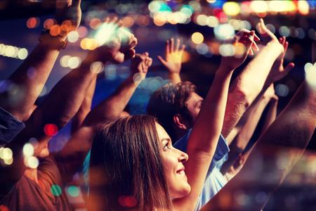 fiesta, días de fiesta, celebración, vida nocturna y la gente concepto - amigos sonrientes que agitan las manos en el concierto en el club