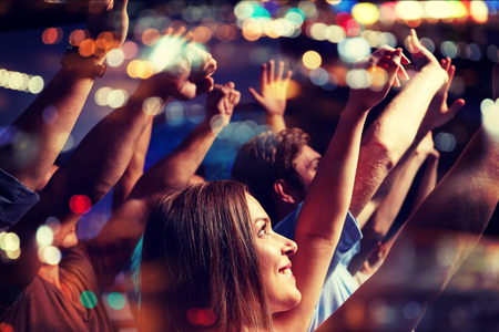 people having fun: party, holidays, celebration, nightlife and people concept - smiling friends waving hands at concert in club