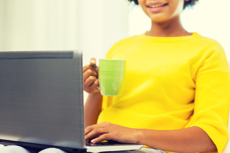 distant: people, technology and leisure concept - close up of happy african american young woman sitting on sofa with laptop computer and drinking tea from cup at home