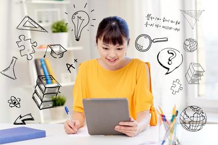 gens, éducation, lycée et concept d'apprentissage - heureux étudiante asiatique jeune femme à lunettes avec tablette pc, livre et bloc-notes à la maison sur doodles