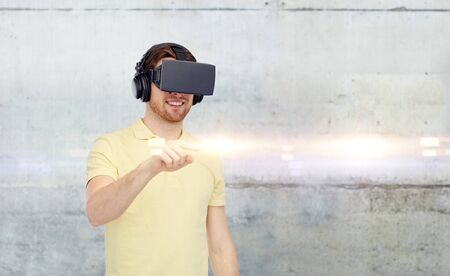 mediated: 3d technology, virtual reality, entertainment and people concept - happy young man with virtual reality headset or 3d glasses playing game over gray concrete wall background Stock Photo