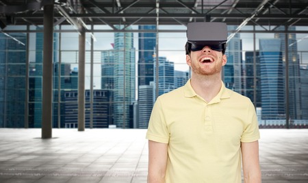 empty of people: 3d technology, virtual reality, entertainment and people concept - happy young man with virtual reality headset or 3d glasses playing game over industrial empty room and city panorama background