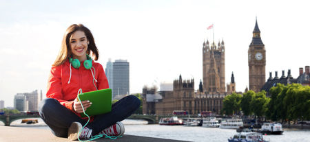 happy smiling: technology, travel, tourism, music and people concept - smiling young woman or teenage girl with tablet pc computer and headphones over london city and big ben tower background