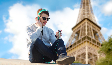 technology, travel, tourism and people concept - smiling young man or teenage boy in headphones with smartphone listening to music over paris eiffel tower background