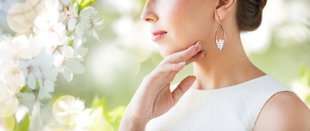 glamour luxury: glamour, beauty, jewelry and luxury concept - close up of beautiful woman face with pearl earring over natural spring cherry blossom Stock Photo