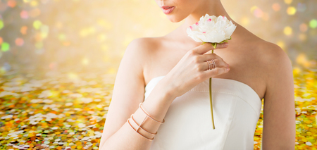 glamour, beauty, jewelry and luxury concept - close up of beautiful woman with golden ring and bracelet holding flower over golden holidays lights background
