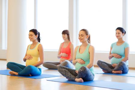 la gravidanza, lo sport, il fitness, la gente e sano concetto di lifestyle - gruppo di donne in stato di gravidanza felice che esercita yoga e meditazione e in posizione del loto in palestra