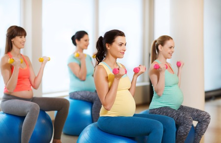 expectation: pregnancy, sport, fitness, people and healthy lifestyle concept - group of happy pregnant women with dumbbells exercising on ball in gym