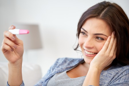 pregnancy, fertility, maternity and people concept - happy smiling woman looking at pregnancy test at home