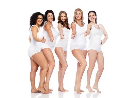 gebaar, vriendschap, schoonheid, lichaam positieve en mensen concept - groep gelukkige verschillende vrouwen in wit ondergoed zien thumbs up