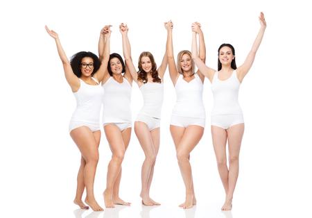 felicidade, amizade, beleza, corpo positivo e conceito dos povos - grupo de mulheres diferentes felizes na roupa interior branca com braços erguidos, comemorando a vitória Foto de archivo