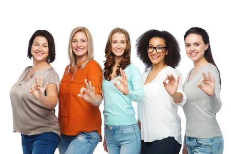 mujeres felices: la amistad, la moda, el cuerpo positivo, el gesto y la gente concepto - grupo de diferentes tamaño de las mujeres felices en ropa casual que muestra la muestra aceptable de la mano