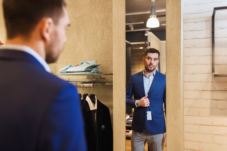 shopaholics: sale, shopping, fashion, style and people concept - elegant young man choosing and trying jacket on and looking to mirror in mall or clothing store Stock Photo