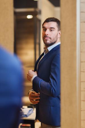 venta, compras, moda, estilo y concepto de la gente - hombre joven y elegante elegir y tratando de chaqueta y mirando al espejo en el centro comercial o tienda de ropa Foto de archivo
