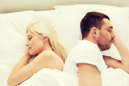 detras de: la gente, el descanso, la hora de acostarse y el concepto de familia - pareja durmiendo de espaldas en la cama en su casa Foto de archivo