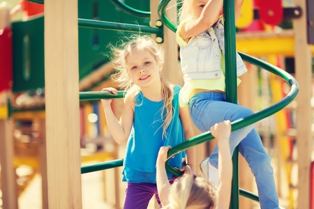 climbing frame: summer, childhood, leisure, friendship and people concept - group of happy kids on children playground climbing frame