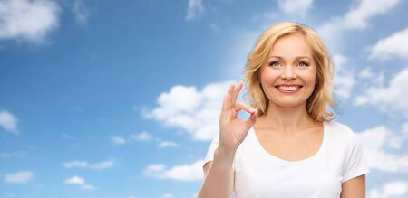 good heavens: gesture, advertisement and people concept - smiling woman in blank white t-shirt showing ok hand sign over blue sky and clouds background Stock Photo
