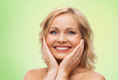 beautiful face woman: beauty, people and skincare concept - smiling woman with bare shoulders touching face over green natural background