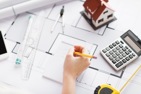 architect tools: business, architecture, building, construction and people concept - close up of architect hand with blueprint and architectural tools writing to notebook Stock Photo
