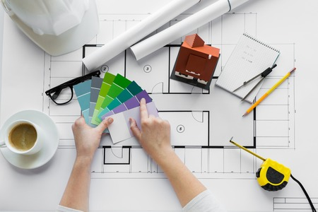business, architecture, building, construction and people concept - close up of designer hands with color palette and house blueprint Archivio Fotografico
