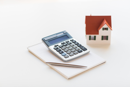 accommodation space: building, mortgage, real estate and property concept - close up of home model, house keys and notebook with pen Stock Photo