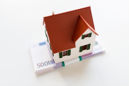 housing prices: building, mortgage, investment, real estate and property concept - close up of home or house model and money Stock Photo