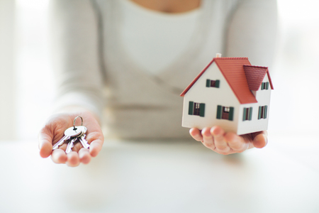 accommodation: building, mortgage, real estate and property concept - close up of hands holding house model and home keys