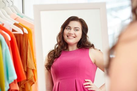 clothing, wardrobe, fashion, style and people concept - happy plus size woman posing at mirror at home Stock Photo
