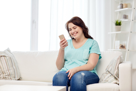 PERSONA LEYENDO: people, technology, communication and leisure concept - happy young plus size woman sitting on sofa with smartphone at home Foto de archivo