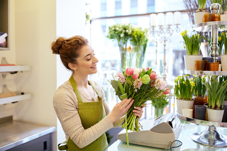 woman shop: people, business, sale and floristry concept - happy smiling florist woman making bunch at flower shop