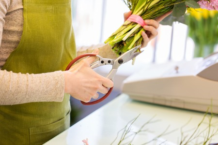 floristry: people, business, sale and floristry concept - close up of florist woman making bunch and cropping stems by scissors at flower shop