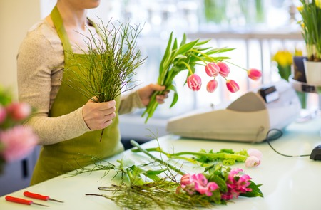 flower shop: people, business, sale and floristry concept - close up of florist woman making tulip bunch at flower shop