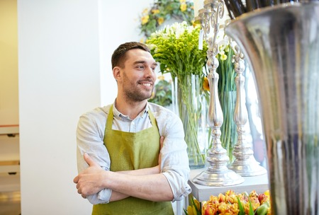 floristry: people, sale, retail, business and floristry concept - happy smiling florist man in apron standing at flower shop