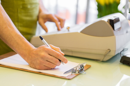 people, sale, retail, business and floristry concept - happy smiling florist man with clipboard and cashbox writing and making notes at flower shop counter Imagens