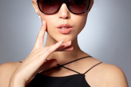 eyewear fashion: accessories, eyewear, fashion, people and luxury concept - close up of beautiful young woman in elegant black sunglasses over gray background