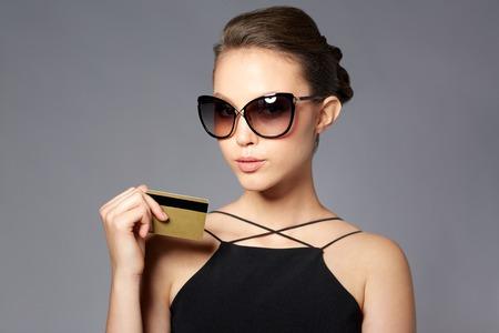 ショッピング、財政、ファッション、人々 および高級コンセプト - 灰色の背景上クレジット カードでエレガントな黒いサングラスで美しい若い女性