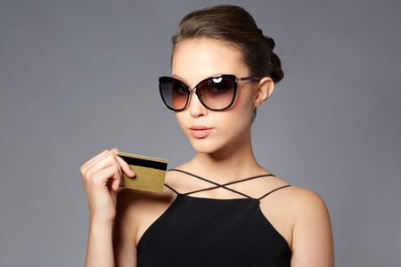 shopping, finances, fashion, people and luxury concept - beautiful young woman in elegant black sunglasses with credit card over gray background Banco de Imagens