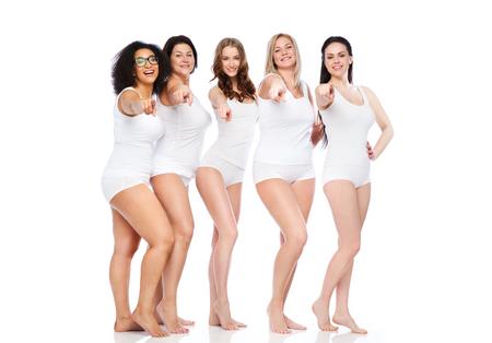 mooie vrouwen: keus, vriendschap, schoonheid, lichaam positieve en mensen concept - groep gelukkige verschillende vrouwen in wit ondergoed wijzende vinger op je