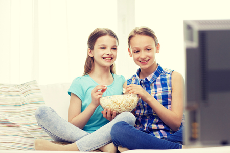friends eating: people, children, television, friends and friendship concept - two happy little girls watching comedy movie on tv and eating popcorn at home Stock Photo