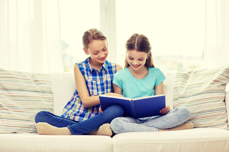 offsprings: people, children, friends, literature and friendship concept - two happy girls sitting on sofa and reading book at home Stock Photo
