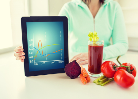 healthy eating, technology, diet and people concept - close up of woman hands holding tablet pc computer with chart, tomato juice and vegetables at home