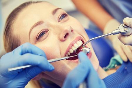 gente, medicina, estomatología y cuidado de la salud concepto - cerca de dentistas y asistente con espejo, taladro y pistola de agua de aire dental rocían el tratamiento de los dientes de los pacientes femeninos en la clínica dental