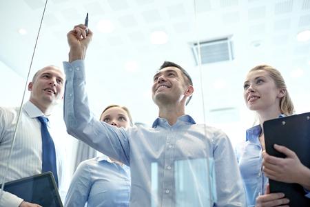 Negocio, la gente, el trabajo en equipo y la planificación concepto - sonriendo equipo de negocios escribir algo que ningún tablón de anuncios con el marcador en el cargo Foto de archivo - 61742980