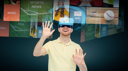 mediated: 3d technology, virtual reality, cyberspace, entertainment and people concept - happy young man with virtual reality headset or 3d glasses networking over black background Stock Photo
