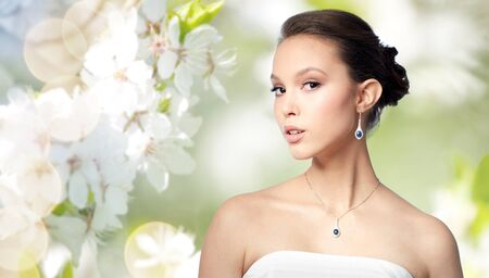 asian natural: beauty, jewelry, wedding accessories, people and luxury concept - beautiful asian woman or bride with earring and pendant over natural spring cherry blossom background Stock Photo