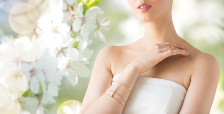 bride bangle: glamour, beauty, jewelry and luxury concept - close up of beautiful woman with golden ring and bracelet over natural spring cherry blossom Stock Photo