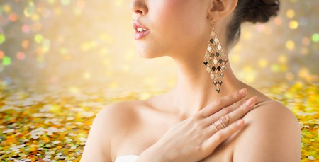 ethnic woman: glamour, beauty, jewelry and luxury concept - close up of beautiful woman with earrings over golden holidays lights background