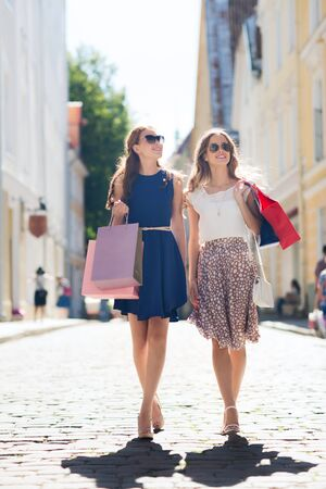 personas en la calle: sale, consumerism and people concept - happy young women with shopping bags walking along city street